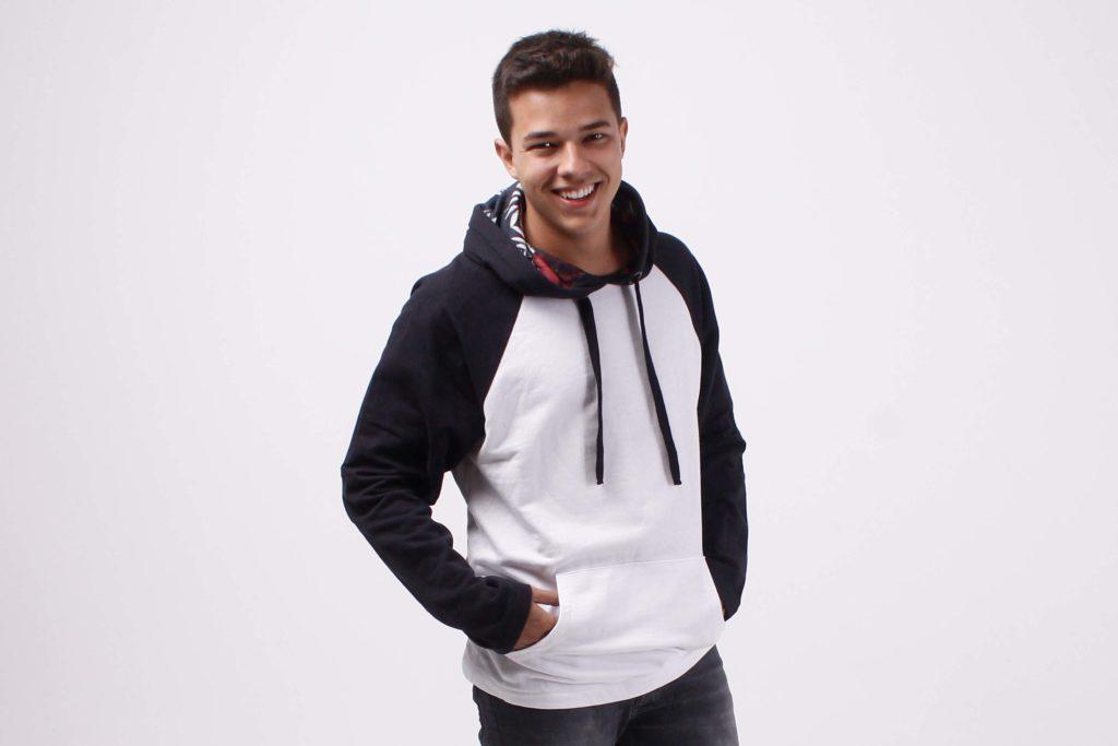 Foto em estudio onde o modelo está vestindo um moletom branco com mangas e capuz preto.