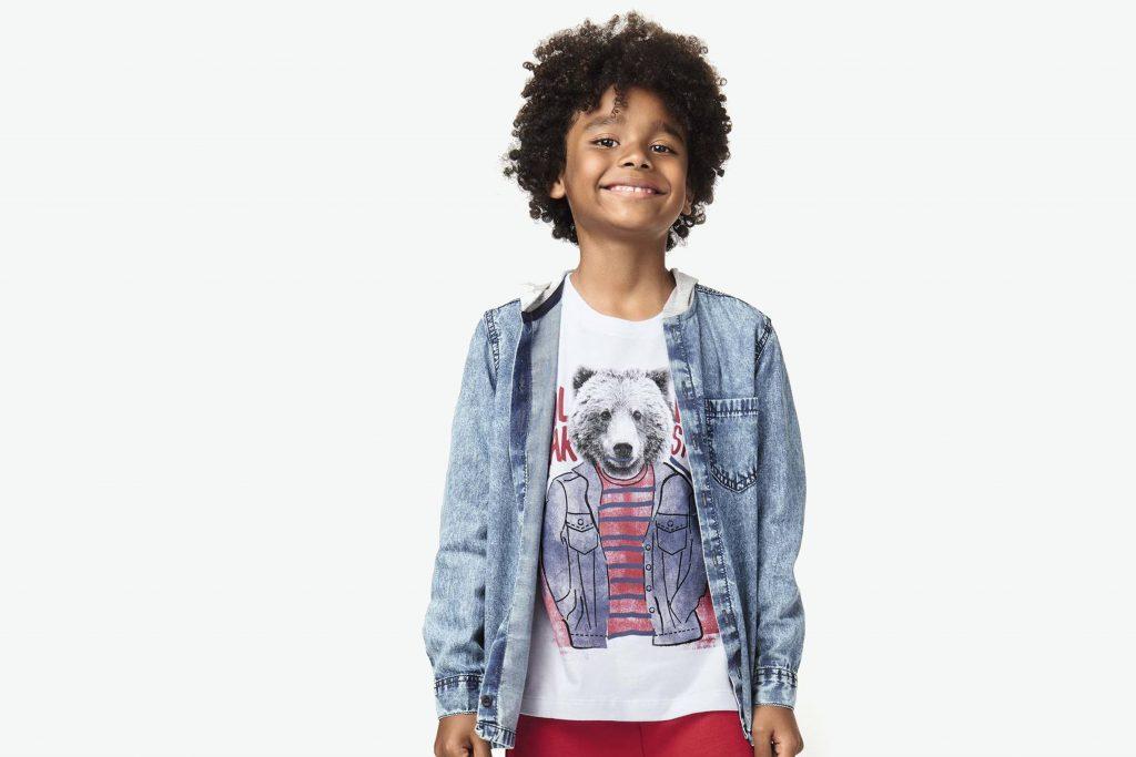 Imagem no estúdio, onde o menino está usando uma camisa jeans e uma camiseta branca com estampa de urso por baixo